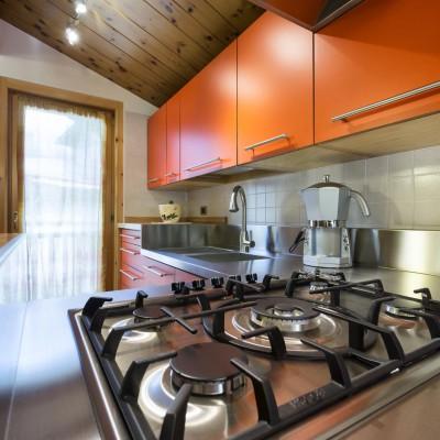 Cucina in legno di faggio con finitura in laminato a tinta unita arancione e piano in acciaio inox