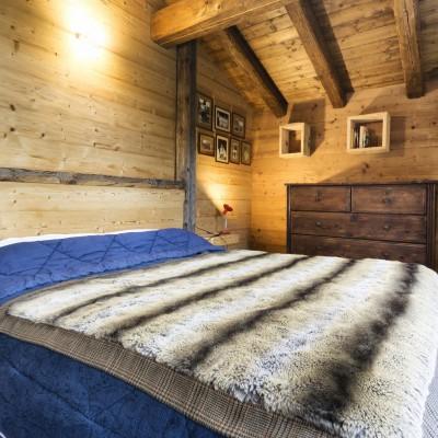 Camera da letto con letto e testata in abete evaporato spazzolato.
